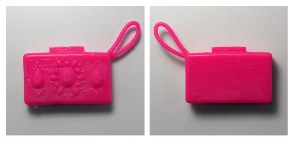 The small hot pink clutch purse has a strap and is patterned on one side