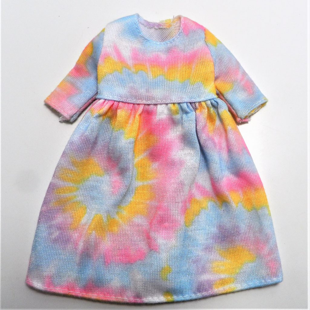 Her dress has soft pastel tie dye patterns and mid length sleeves
